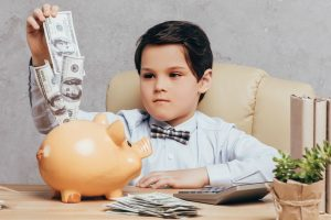 caucasian boy sitting at a desk and putting money into a piggybank