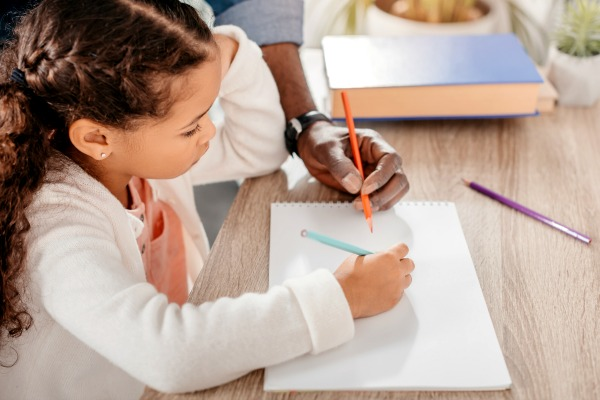 African American girl doing homeschool work at table with parents hand writing on a paper