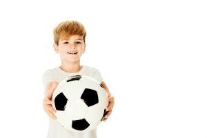 caucasian boy holding a soccer ball in front of him