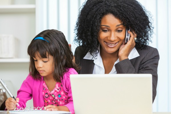 Beautiful middle aged African American woman or businesswoman working on her cell phone & laptop computer and looking after her female child daughter working on homeschool work