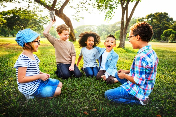 young kids of different ethnicities sitting on the grass and laughing