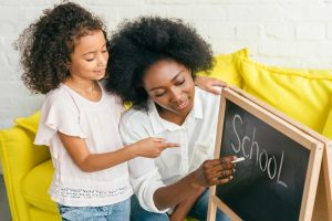 African american mom writing the word school on a small chalk board at home for her African American daughter