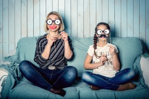 mother and daughter sitting on couch and holding up paper glasses and moustaches to face